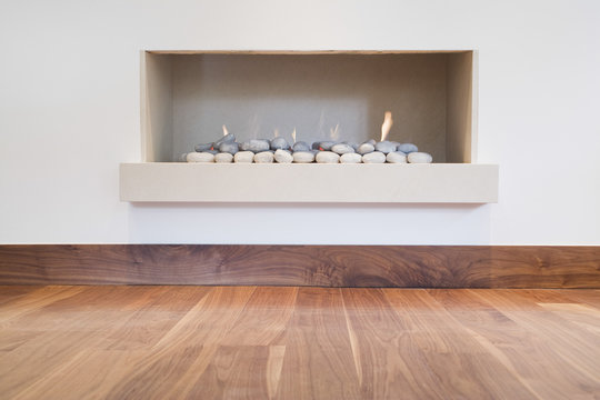 Detail shot of a modern simple fireplace with hardwood floor