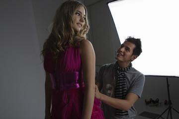 Male designer adjusting dress on a fashion model in studio
