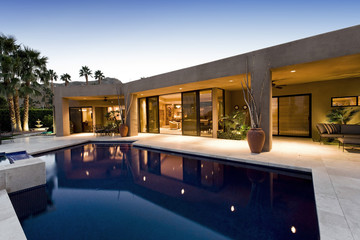 View of swimming pool in front of a modern house against clear sky