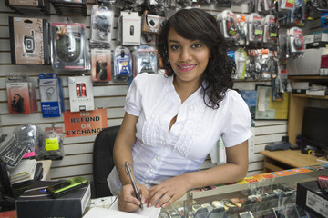 Portrait of young Hispanic Latin female owner making a bill at mobile store