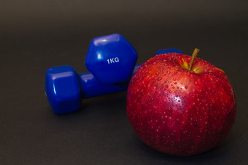 red apple with blue dumbbells on a black