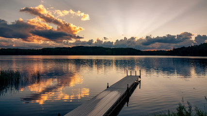 A dock jutts out into a lake at sunset on a northern Wisconsin lake.