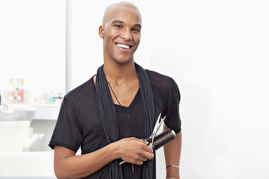 Portrait of happy male stylist holding hairbrush and scissors