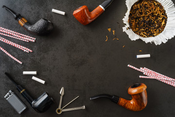 Collection of pipes and smoking utensils with copyspace in the middle