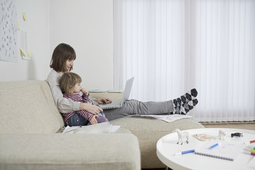 Side view of a mother and daughter with laptop in the living room
