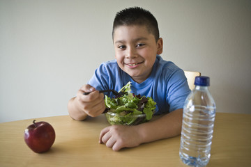 Portrait of a happy obese preadolescent boy eating salad