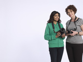 Portrait of two multiethnic women holding digital cameras in studio