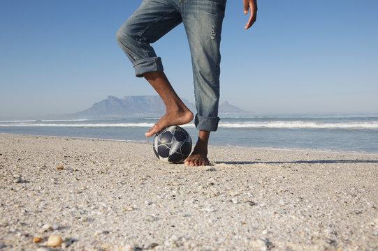 Lowsection of a man with foot on soccer ball at beach
