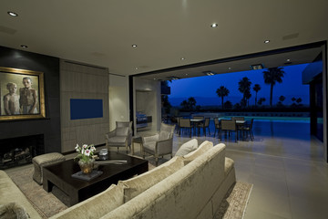 Modern living room with view of swimming pool and patio at dusk