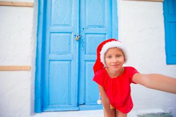 Adorable litttle girl in Santa Hat taking selfie at narrow street in greek village