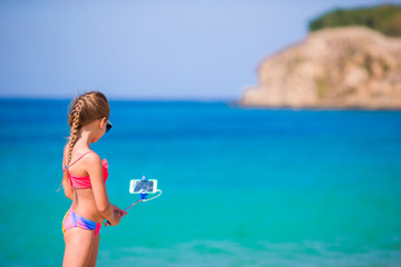 Little girl taking selfportrait by cellphone on the beach. Kid enjoying her suumer vacation and making photos background the sea