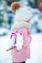 Adorable little girl going skating in winter snow day outdoors