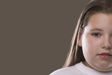 Closeup of an overweight serious girl against gray background