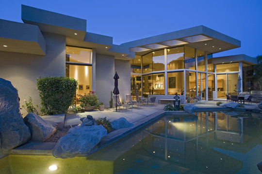 Illuminated house exterior with swimming pool in backyard at dusk