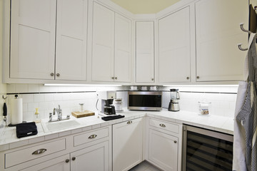 Closeup of white cabinets with oven and coffee machine at the kitchen