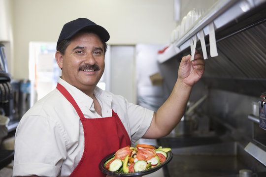 Portrait of Hispanic Latin man with served food standing in restaurant kitchen