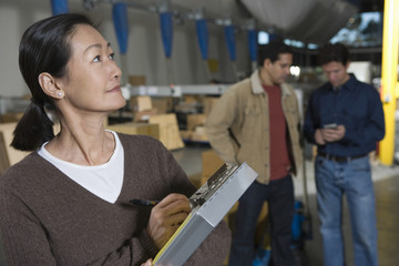 Asian woman making notes with workers in background at distribution warehouse