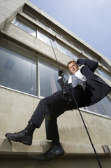 Low angle view of a spy rappelling while using mobile phone