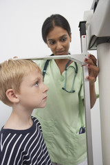 Female doctor measuring height of a boy in the clinic