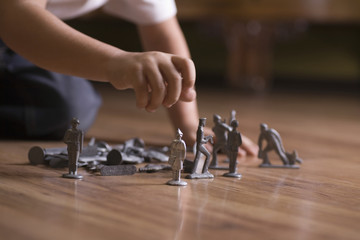 Closeup of a cropped boy playing with toy soldiers on floor