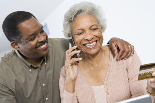 Happy African American couple shopping online through credit card