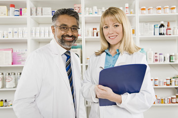 Portrait of two happy pharmacists standing at drugstore