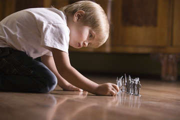 Side view of a young boy playing with toy soldiers on floor