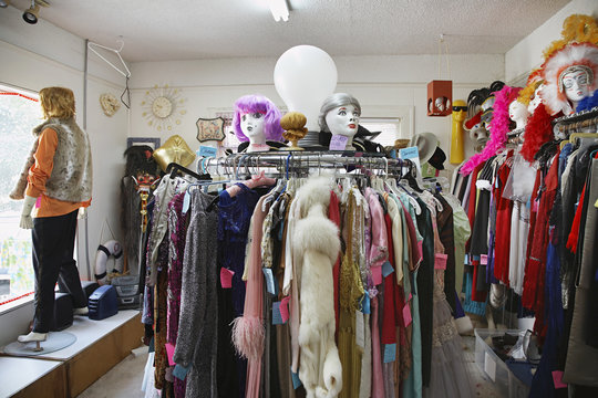 View of clothing and wigs in a crowded second hand store