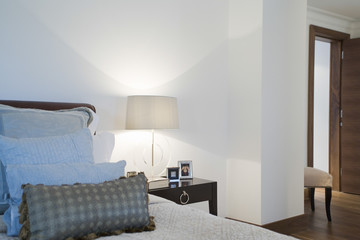 Framed photographs and lamp on side table in bedroom