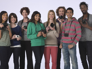 Group portrait of multiethnic young people holding cameras in studio