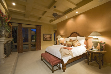 View of lit lamps by bed in spacious bedroom