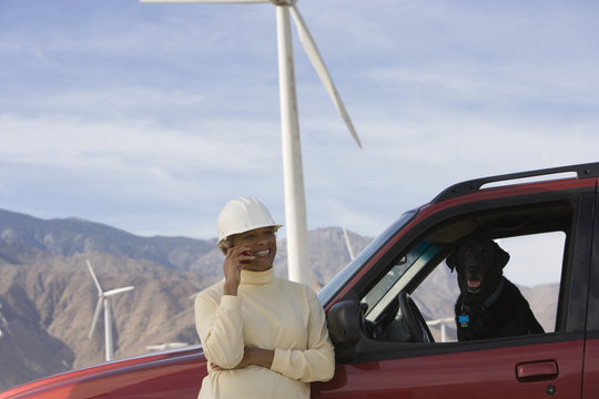 Happy mature female using cellphone at windfarm