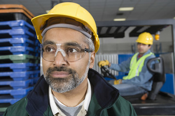 Serious man in hardhat and goggles with colleague in the background at factory