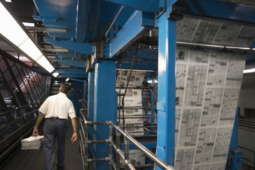 Rear view of a man carrying stack of newspapers in the factory