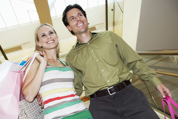 Low angle view of a happy couple with shopping bags on staircase in mall
