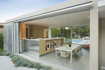 Kitchen and dining area from outdoors with swimming pool in background Fototapete