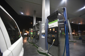 Closeup of cropped car at gas station with view of fuel pumps and natural gas at night