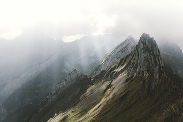 Mountain range in the alps with dramatic sky and rays of light