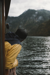Young adult male wearing yellow and blue jacket and cap looking out of a boat window on a mountain lake