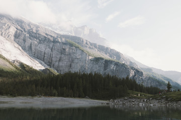 Mountain range and pine forest reflected in a still and calm lake under a hazy and cloudy sky at daylight