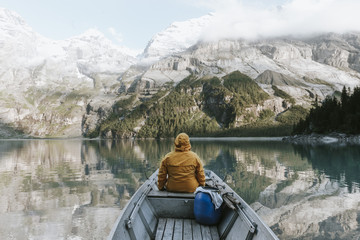 Adult male wearing a yellow jacket sitting in a boat at a mountain lake reflecting the forest and sky in the background