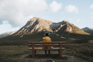 Young male wearing a yellow coat sitting on a bench and viewing a mountain and clouds in the distance at moody daylight