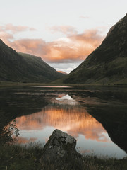 Sunset in the mountains at a calm lake reflecting the red and orange sky symmetrically and mirror like