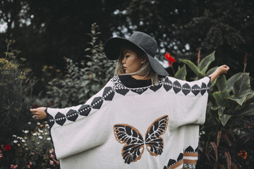 Young asian Woman wearing a fashionable hat and poncho surrounded by flowers