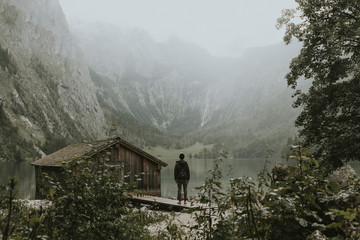 Young adult man standing by a foggy and moody lake near a boat house surrounded by forest with mountains in the background