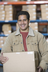Portrait of a man carrying cardboard box in distribution warehouse