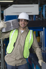 Portrait of a smiling industrial operator carrying newspapers in factory