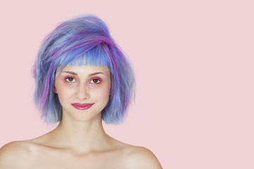 Portrait of beautiful young woman with dyed hair against pink background