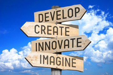 Wooden signpost with four arrows - develop, create, innovate, imagine.