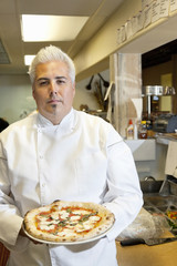 Portrait of a confident mid adult chef holding pizza in commercial kitchen